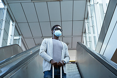 Male entrepreneur wearing protective face mask holding luggage while standing on escalator at station - p300m2241545 von Pete Muller