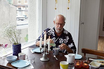 Senior man sitting at table - p312m2080166 by Johanna Nyholm
