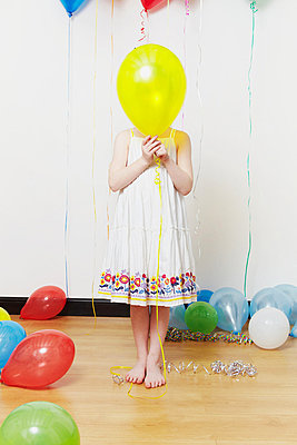 Girl holding balloon in front of face - p92411551f by Emma Kim