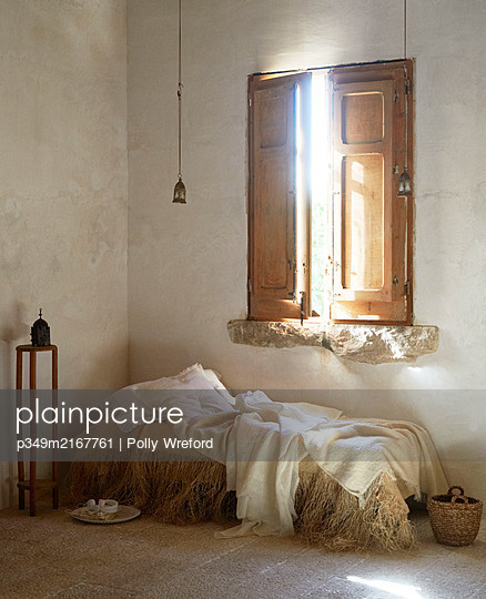 Unmade daybed below closed wooden shutters in Sicilian home - p349m2167761 by Polly Wreford