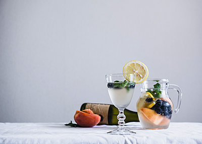 Cold drinks in glass and jug on table against white wall - p1166m1070886f by Miki Fujii