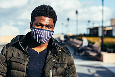 Portrait of an African American boy with a face mask in an urban space. - p1166m2254929 by Cavan Images