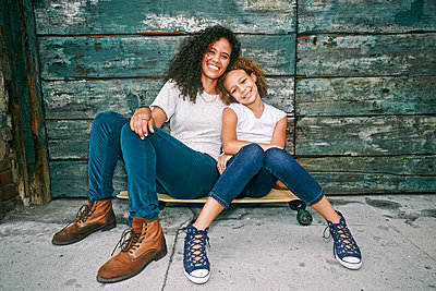 Mixed race mother and daughter sitting on skateboard - p555m1410417 by Peathegee Inc