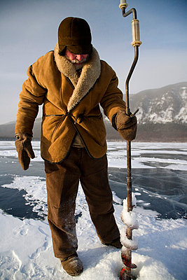 Undergoing preparations for fishing on frozen lake baikal in winter - p6521678 by Ken Scicluna
