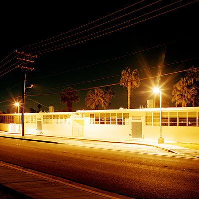 A street and building at night, long exposure, Palm Springs, CA - p1094m900230 by Patrick Strattner
