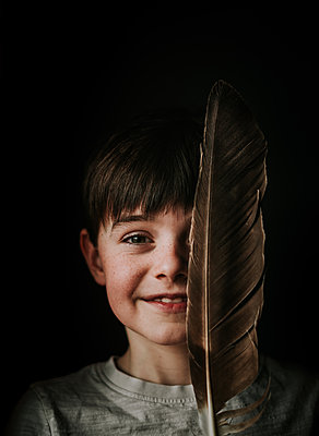 Portrait of young boy holding a large feather over half of his face. - p1166m2095921 by Cavan Images