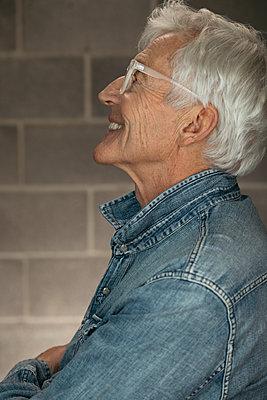 Profile carefree, happy senior man in denim shirt - p1192m1529876 by Hero Images