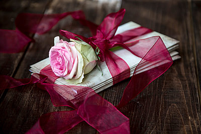 Stack of old love letters and rose blossom tied with red ribbon - p300m1113435f by Sandra Roesch