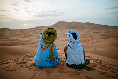Woman sitting in the desert with Berber guide, watching sunset - p300m1166380 by Kiko Jimenez