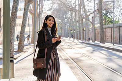 Portrait of smiling young woman with smartphone at the tram stop - p300m2166179 by VITTA GALLERY