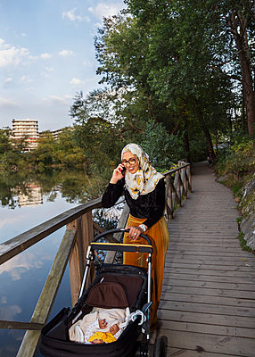 Woman talking via cell phone while pushing pram - p312m2239647 by Pernille Tofte