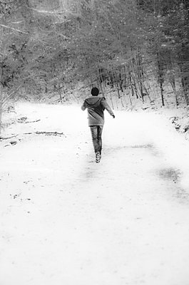 Young Man in Winter Coat Running Along Snow-Covered Woodsy Path - p694m910687 by Eric Schwortz