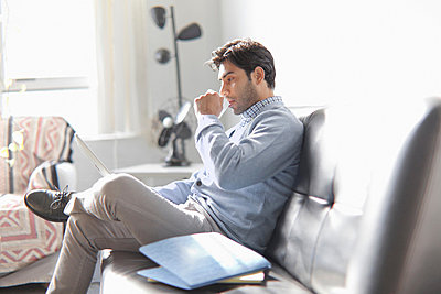 Man using laptop on sofa - p924m757033f by Chad Springer