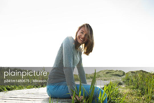 Young woman on planked footpath in the dunes - p341m1480675 by Mikesch