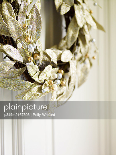Christmas wreath with gold leaves and mistletoe berries - p349m2167808 by Polly Wreford