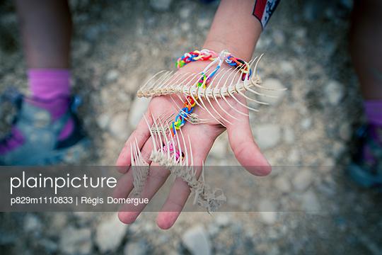 Kind hält Fischskelett in der Hand - p829m1110833 von Régis Domergue