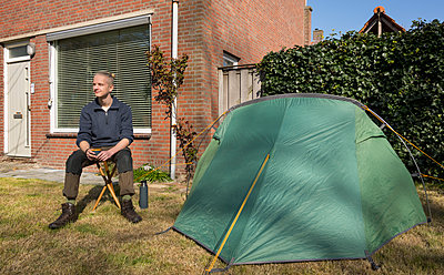 Young man sits in the front garden next to a small tent - p1132m2176561 by Mischa Keijser
