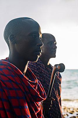 Two masai men in traditional clothes standing in front of sea - p1166m2157029 by Cavan Images