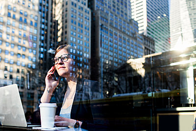 Businesswoman using phone seen through window with reflection of building - p1264m1172942 by Astrakan