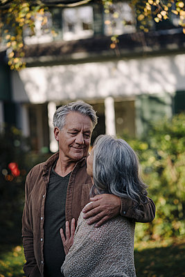 Affectionate senior couple in garden of their home in autumn - p300m2156102 by Gustafsson