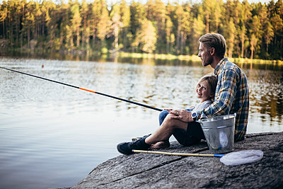 Portrait of smiling daughter fishing with father while sitting by lake - p426m2212175 by Maskot