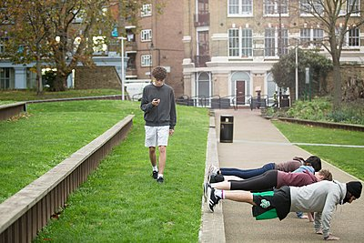 Group of adults exercising outdoors, young man looking at stopwatch - p429m1106677f by Franek Strzeszewski