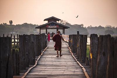 Buddhist Monk on U Bein Teak Bridge at sunrise, Mandalay, Mandalay Region, Myanmar , Asia - p871m1107233 by Matthew Williams-Ellis