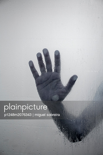 Man's Hand Pressed Against Shower Screen - p1248m2076343 by miguel sobreira