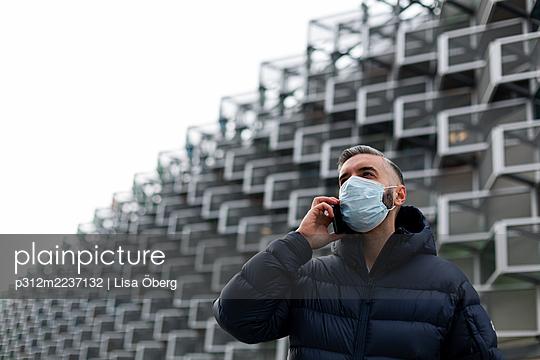Man wearing face mask talking via cell phone - p312m2237132 by Lisa Öberg