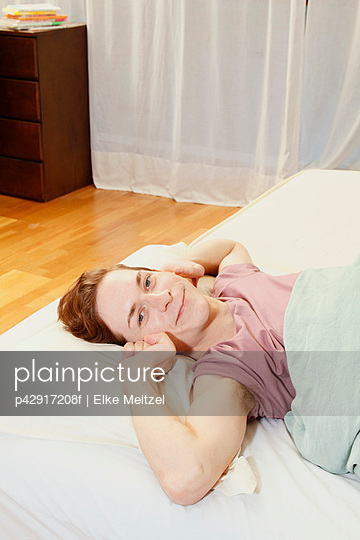Smiling man stretching in bed - p42917208f by Elke Meitzel
