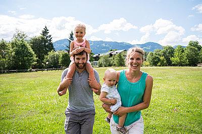 Junge Familie mit zwei Töchtern spazieren auf Wiese - p1142m2109444 von Runar Lind
