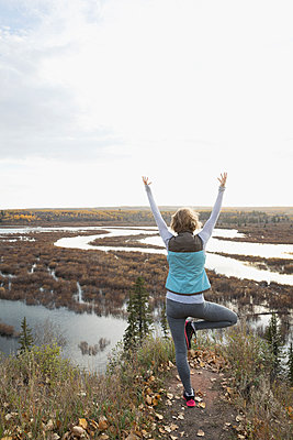 Woman practicing yoga tree pose on autumn hilltop overlooking lake - p1192m1194122 by Hero Images