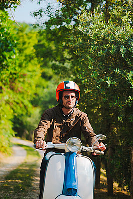 Portrait of man riding vintage motor scooter, Tuscany, Italy - p300m2167150 by Giorgio Fochesato