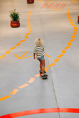 Blond woman skateboarding on footpath with orange road marking - p300m2221599 by Manu Reyes