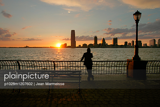 Sunset over Lower Manhattan with Jersey City in the distance - p1028m1207602 by Jean Marmeisse
