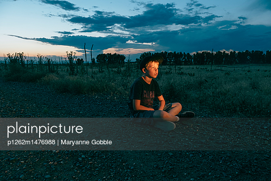 Boy sitting on gravel road at dusk - p1262m1476988 by Maryanne Gobble