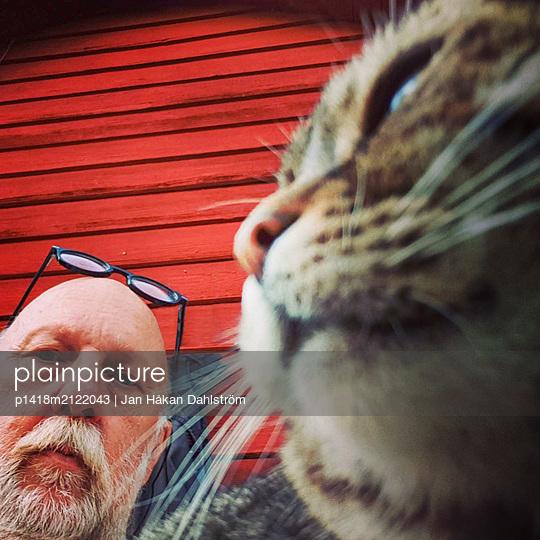 Elderly man and cat - p1418m2122043 by Jan Håkan Dahlström