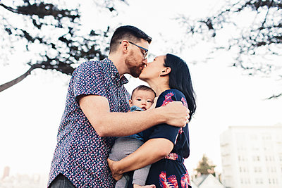 Low angle view of couple with daughter kissing while standing against clear sky in city - p1166m1530760 by Cavan Images
