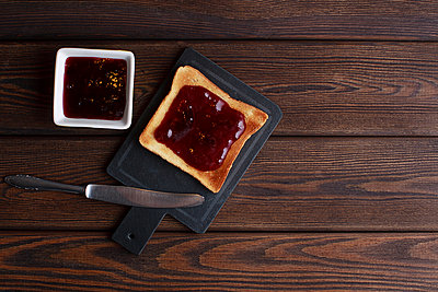 Toasts with jam on dark wooden table - p1166m2169188 by Cavan Images