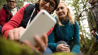Active senior hiker friends using camera phone - p1192m2000421 by Hero Images