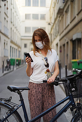 a masked woman writes a text on her phone - p1610m2208790 by myriam tirler