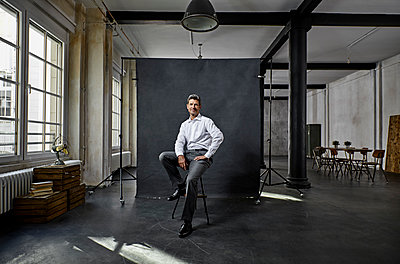 Portrait of mature businessman in front of black backdrop in loft - p300m1580702 von Philipp Dimitri