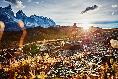 Chile, Torres del Paine National park, man standing in front of Torres del Paine massif at sunrise - p300m2069848 by Stefan Schütz