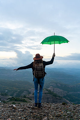 Woman standing on a mountain, looking at view, holding a green umbrella - p300m2079028 von VITTA GALLERY