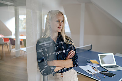 Portrait of young businesswoman in office with table tennis table - p300m2160143 by Gustafsson