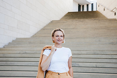 Smiling mature female professional holding blazer against staircase - p300m2256153 by Katharina Mikhrin