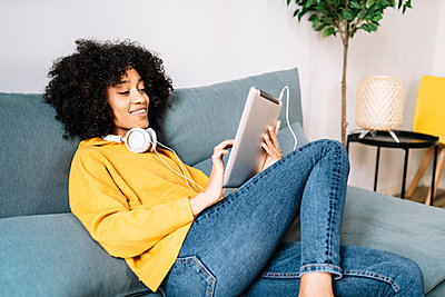 Relaxed young woman using digital tablet while sitting on sofa at home - p300m2275374 by COROIMAGE