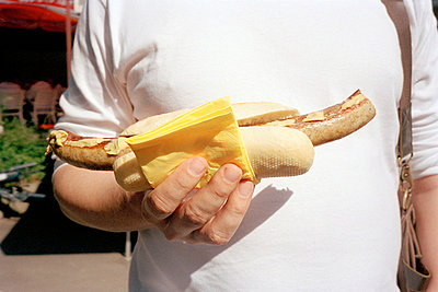 Man holding hot dog - p3880384 by Ulrike Leyens