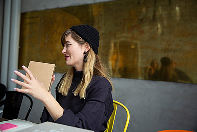 Smiling businesswoman with product box sitting in creative office - p426m2270392 by Maskot