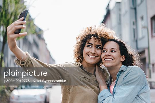 Best friends taking selfies with a smartphone in the city - p300m2012778 von Kniel Synnatzschke